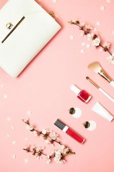 Mode concept. cosmetische producten die voortvloeien uit make-up tas op pastel roze pagina