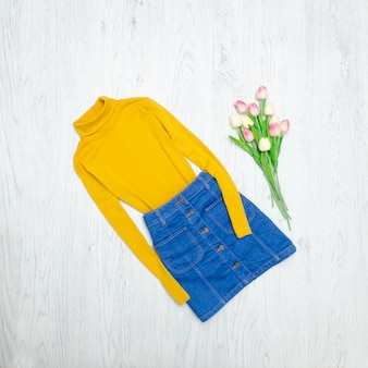 Mode concept. gele coltrui, blauwe rok en roze tulpen. hout achtergrond