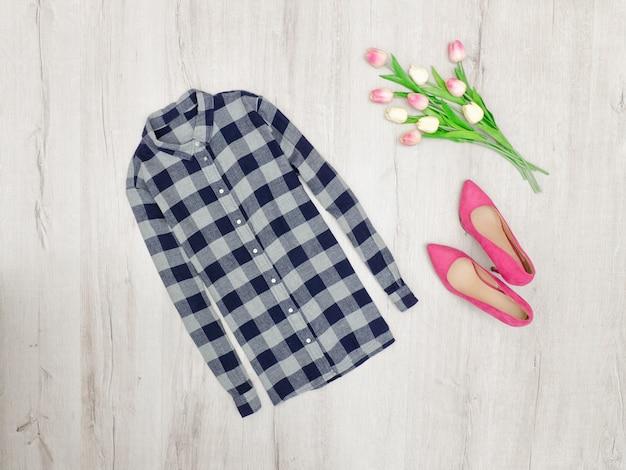 Mode concept. geruit hemd, roze schoenen en tulpen. bovenaanzicht