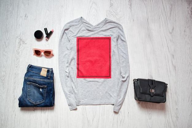 Mode concept. grijs jasje met rode rechthoek, blauwe spijkerbroek, zwarte tas, zonnebril, lippenstift. lente kleerkast.