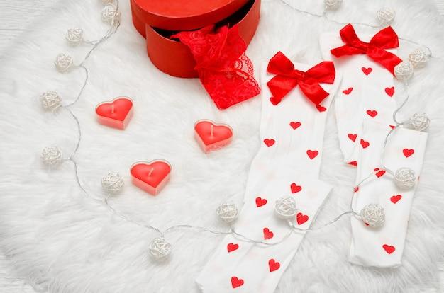 Mode concept. kaarsen in de vorm van hart, witte kousen met rode strikdoos met kanten linnen,