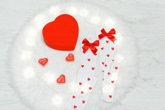 Mode concept. witte kousen en doos in de vorm van een hart. witte vacht