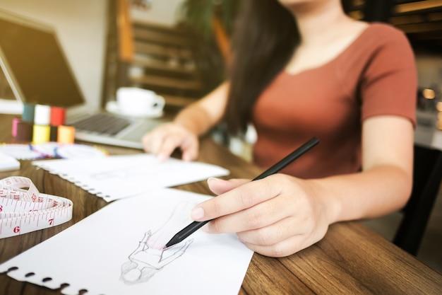 Mode / creatieve ontwerper die met het schetsen van notitieboekje bij moderne huisstudio werken, selectieve nadruk