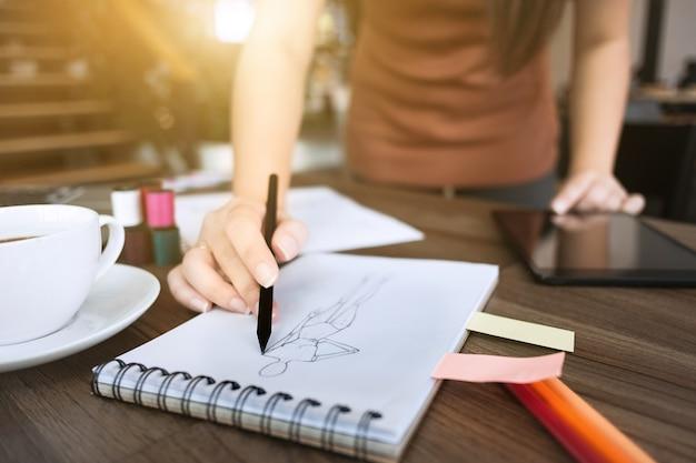 Mode / creatieve ontwerper werken met schetsend notitieboekje in moderne thuisstudio, selectieve focus