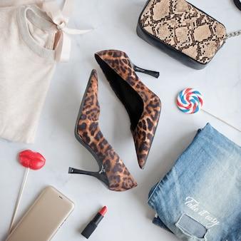 Mode dame kleding set. stijlvolle slangenhandtas clutch, trendy luipaardschoenen. plat lag op een witte achtergrond