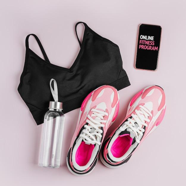 Mode dames sneakers met smartphone op een roze achtergrond. online trainingsprogramma