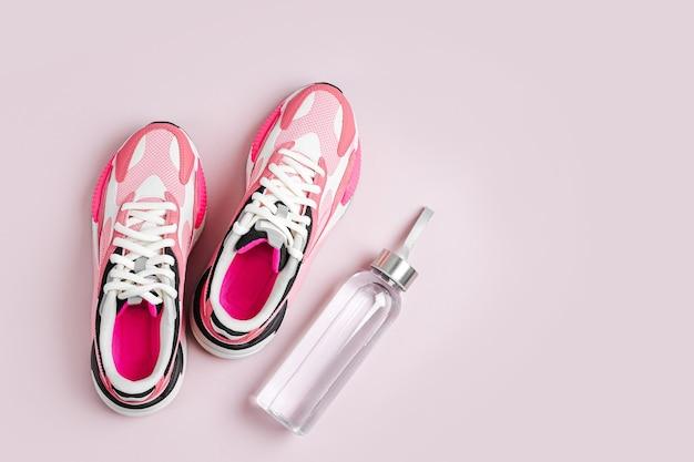 Mode dames sneakers met waterfles op een roze achtergrond. vrouwelijke sportschoenen.