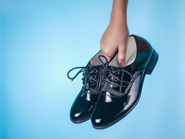 Mode damesschoenen met veters in baby's hand op blauwe ondergrond. stijlvolle en modieuze leren damesschoenen.