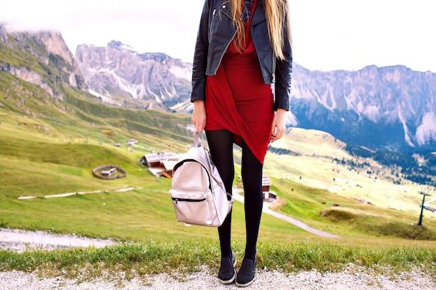 Mode details van stijlvolle toeristische vrouw poseren eten elegante jurk leren jas en trendy rugzak, modieuze luxe vakantie in alp gebergte.