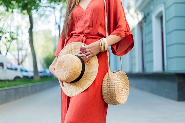 Mode details. vrouw in geweldige stijlvolle koraal zomerjurk poseren op straat