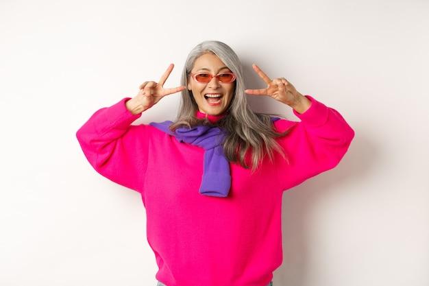 Mode en beauty concept. afbeelding van een stijlvolle aziatische senior vrouw met een zonnebril die lacht, vredestekens toont en er gelukkig uitziet, staande op een witte achtergrond