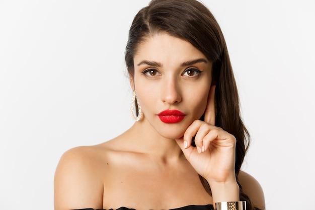 Mode en beauty concept. close-up van elegante mooie vrouw in zwarte jurk, avond make-up en rode lippenstift, brutaal camera kijken, staande op witte achtergrond.