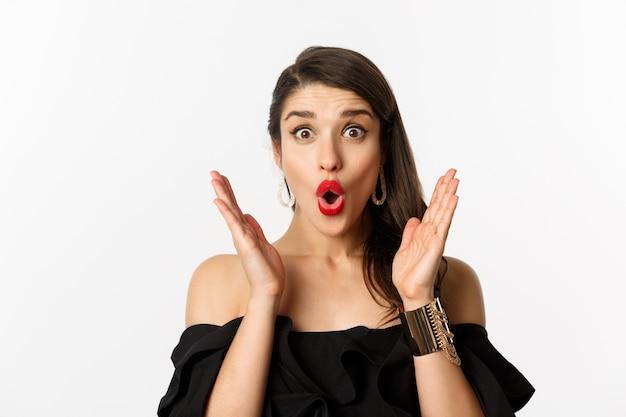 Mode en beauty concept. close-up van opgewonden vrouw met make-up en rode lippenstift, op zoek verrast en blij, staande op witte achtergrond.