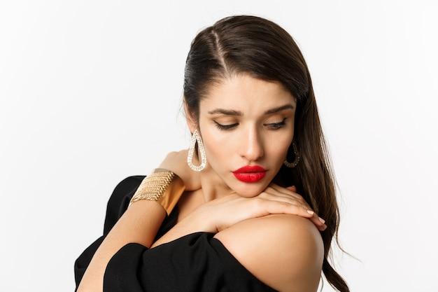 Mode en beauty concept. close-up van sensuele vrouw in elegante oorbellen en zwarte jurk, make-up met rode lippen dragen, teder neerkijkt, staande op witte achtergrond.