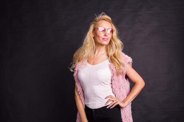 Mode en beauty concept - portret van blond model gekleed in wit overhemd en roze vest voorbij