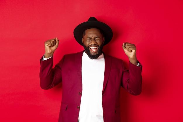 Mode en feestconcept. opgewonden zwarte man die prijs wint, handen schudden en overwinning vieren, nieuwjaar vieren, staande tegen rode achtergrond