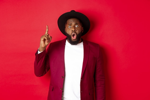 Mode en feestconcept. opgewonden zwarte man met een idee, vinger opsteken om suggestie te zeggen, staande in stijlvolle hoed en blazer, rode achtergrond.