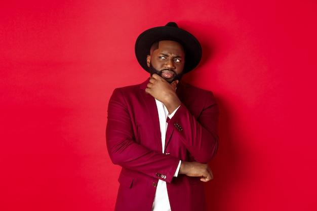 Mode en feestconcept. sceptische en twijfelachtige afro-amerikaanse man die denkt, ontevreden kijkt in de linkerbovenhoek, twijfelt, rode achtergrond.