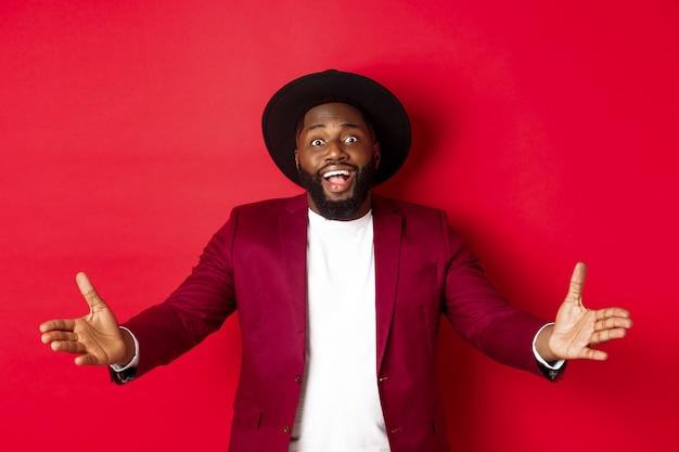 Mode en feestconcept. tevreden knappe zwarte man spreidde zijn handen in een welkom gebaar, reikte om iets te ontvangen, keek verbaasd, stond op een rode achtergrond