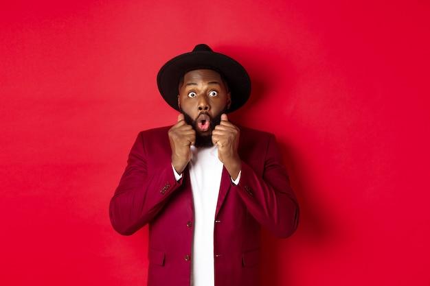 Mode en feestconcept. verrast afro-amerikaans mannelijk model dat geschokt en verbaasd kijkt, wow zegt en camera staart, staande tegen een rode achtergrond