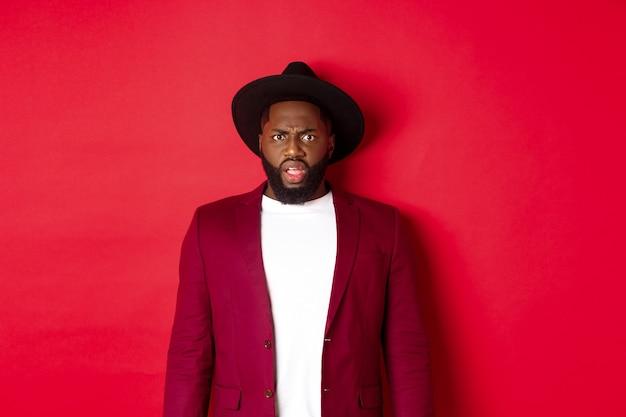Mode en feestconcept. verward zwarte man in stijlvolle outfit fronsend en starend naar camera ontevreden, kan het niet begrijpen, staande over rode achtergrond