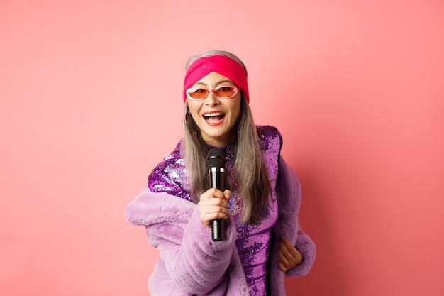 Mode en lifestyle concept. mooie vrouw van middelbare leeftijd in zonnebril, feestjurk en namaakbontjas, zingen in de microfoon en plezier hebben in de karaokebar, roze achtergrond.