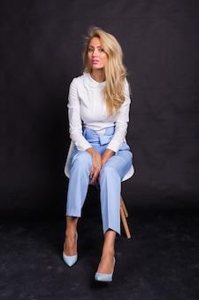 Mode en mensen concept - jonge blonde lachende vrouw zittend op de stoel over de zwarte