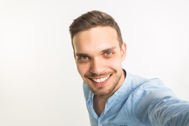 Mode en mensen concept - knappe man maken een selfie foto en lachend op een witte achtergrond.