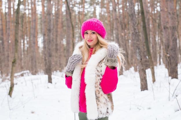 Mode en mensen concept - mooie jonge vrouw in warme jas in winter park
