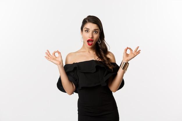 Mode en schoonheid. aantrekkelijke brunette vrouw in zwarte jurk, ok tekenen tonen en opgewonden staren, goedkeuren en aanbevelen, staande op witte achtergrond.