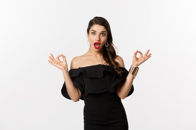 Mode en schoonheid. aantrekkelijke brunette vrouw in zwarte jurk, oke tekenen en opgewonden staren, goedkeuren en aanbevelen, staande op een witte achtergrond.