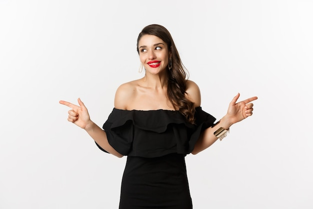 Mode en schoonheid. aantrekkelijke vrouw in sieraden, make-up en zwarte jurk, glimlachend en wijzende vingers zijwaarts kopiëren ruimteaanbieding, witte achtergrond.