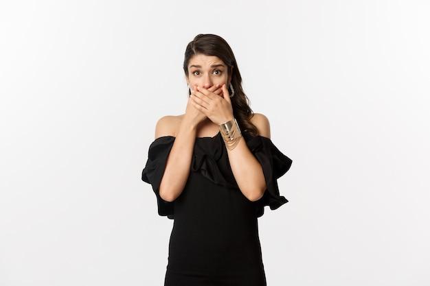 Mode en schoonheid. aantrekkelijke vrouw in zwarte jurk bedek mond en hijgend geschokt, starend naar camera bezorgd, staande over witte achtergrond
