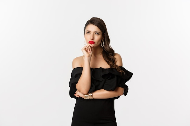 Mode en schoonheid. afbeelding van een doordachte glamourvrouw die wegkijkt, turen terwijl ze nadenkt, staande in zwarte jurk tegen een witte achtergrond.