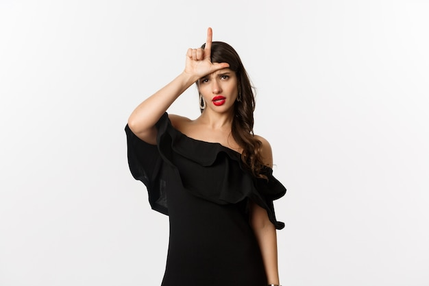 Mode en schoonheid. arrogante glamourvrouw die verliezersteken op voorhoofd toont, spottende verloren persoon, die zich in zwarte kleding over witte achtergrond bevindt.