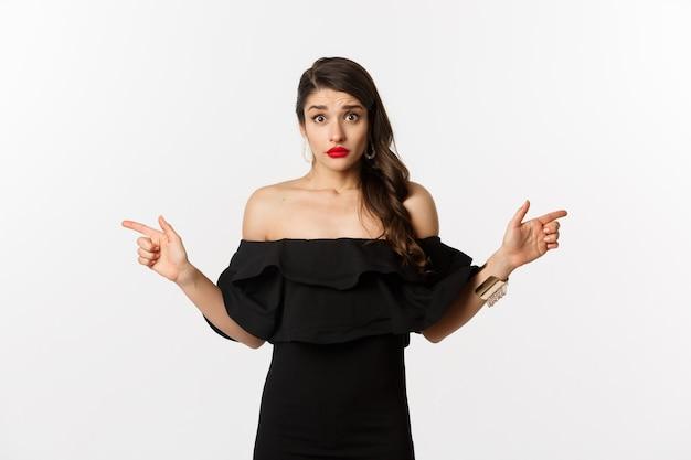 Mode en schoonheid. besluiteloze jonge vrouw in zwarte glamourjurk die met de vingers zijwaarts wijst, twee keuzes laat zien en er verward uitziet, witte achtergrond