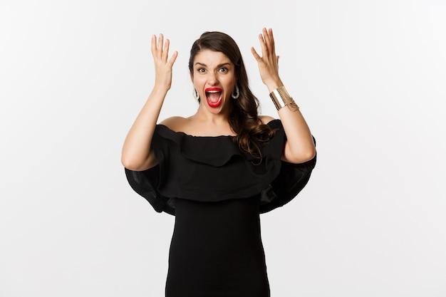 Mode en schoonheid. boze vrouw in zwarte jurk, boos schreeuwen en handen schudden, grimassen woedend op camera, staande op witte achtergrond.