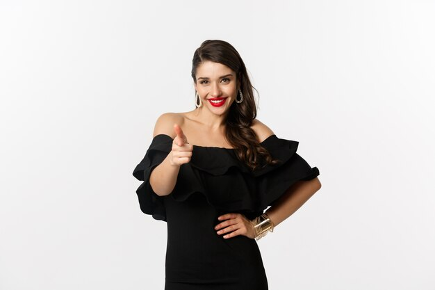 Mode en schoonheid. brutale mooie vrouw in zwarte jurk en make-up, wijzende vinger op camera om te feliciteren of te prijzen, staande op een witte achtergrond.