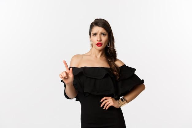 Mode en schoonheid. brutale vrouw in zwarte jurk die nee zegt, oneens is en ontevreden vinger schudt, aanbod afwijst, iets afwijst, staande op een witte achtergrond.
