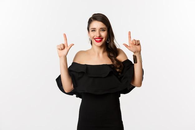 Mode en schoonheid. charmante vrouw met rode lippen, zwarte jurk, glimlachend gelukkig en wijzende vingers omhoog, logo, witte achtergrond weergegeven.