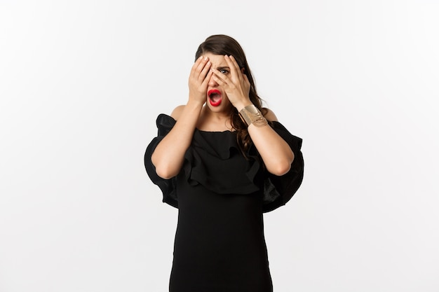 Mode en schoonheid. geschokt jonge vrouw in zwarte jurk voor ogen, gluren door vingers naar iets gênants, ineenkrimpen, staande op witte achtergrond.