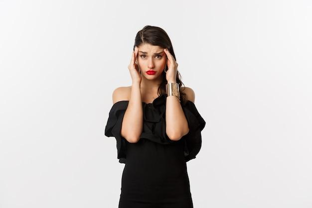 Mode en schoonheid. jonge moderne vrouw in glamourjurk, sieraden en make-up, hoofd aanraken en uitgeput kijken, duizelig voelen, staande op witte achtergrond.