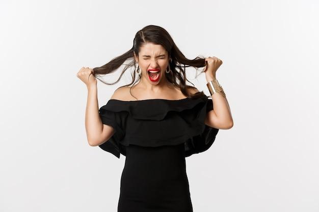 Mode en schoonheid. jonge vrouw in zwarte jurk schreeuwen en haar scheuren op het hoofd, gek schreeuwen, staande boos en verontwaardigd over witte achtergrond.