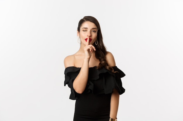 Mode en schoonheid. koket jonge vrouw in zwarte jurk, rode lippen, knipogen naar de camera en stilte teken maken, staande op witte achtergrond.