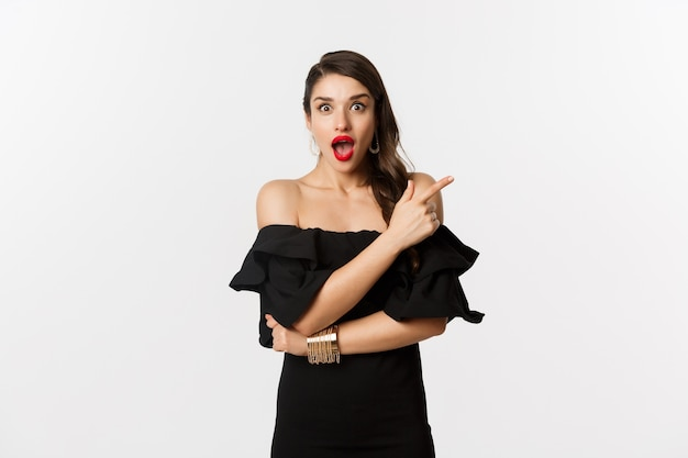 Mode en schoonheid. mooie vrouw in zwarte jurk, rode lippen, wijzende vinger rechts op promo-aanbieding, camera, witte achtergrond verbaasd kijken.