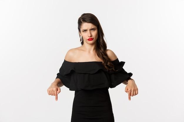 Mode en schoonheid. ontevreden vrouw die klaagt, fronst en met de vingers naar beneden wijst, drukt teleurstelling en afkeer uit, witte achtergrond.