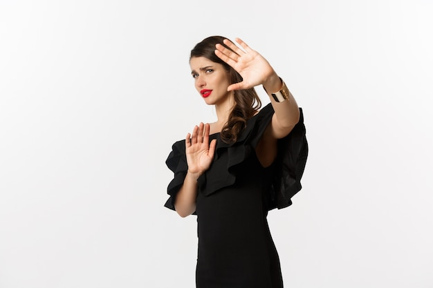 Mode en schoonheid. onwillige en bezorgde vrouw die vraagt weg te blijven, stopgebaar toont en bang kijkt, staande in zwarte jurk op witte achtergrond.