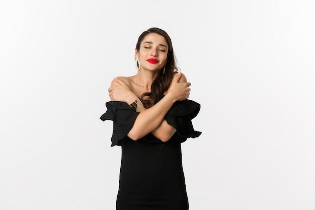 Mode en schoonheid. sensuele en mooie vrouw in zwarte jurk, zichzelf knuffelen met gesloten ogen, dagdromen, staande op een witte achtergrond