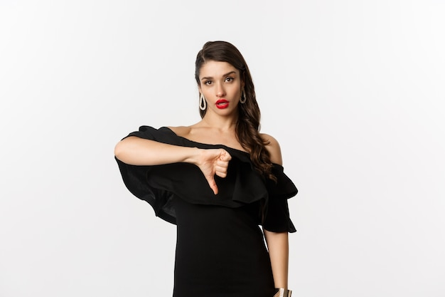 Mode en schoonheid. teleurgestelde brutale vrouw in zwarte jurk, met duimen naar beneden, houdt niet van iets slechts, te oordelen over witte achtergrond.
