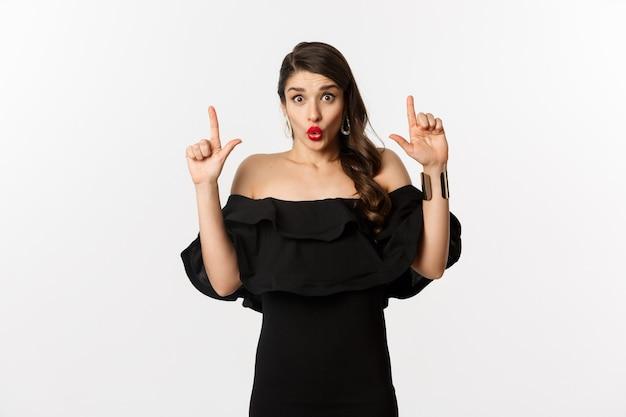 Mode en schoonheid. verraste vrouw die advertentie bovenaan toont, met de vingers omhoog wijst en wow verbaasd zegt, staande op een witte achtergrond